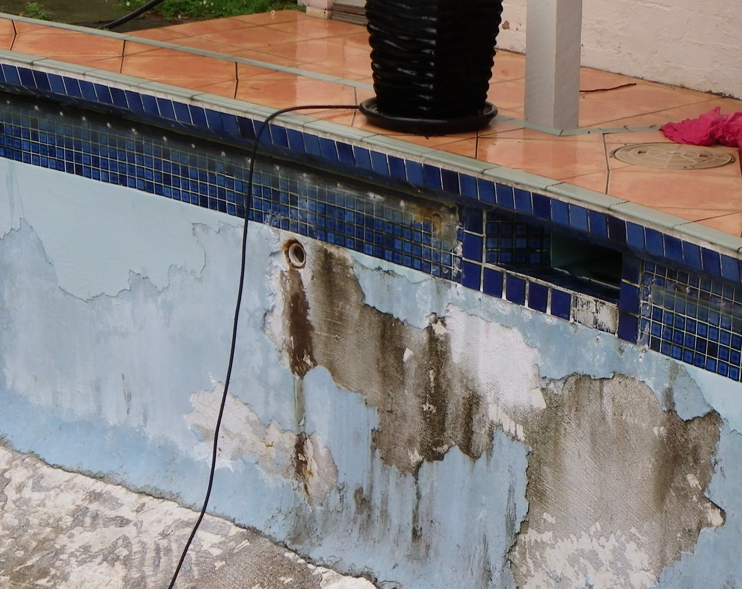 Effects of poor drainage around pool and causing in part delamination of render.